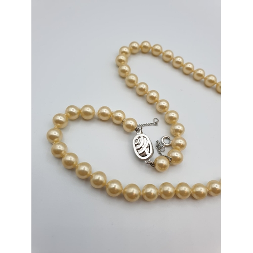 47 - String of cultured pearls with ornate silver clasp, weight 30g and 45cm length...