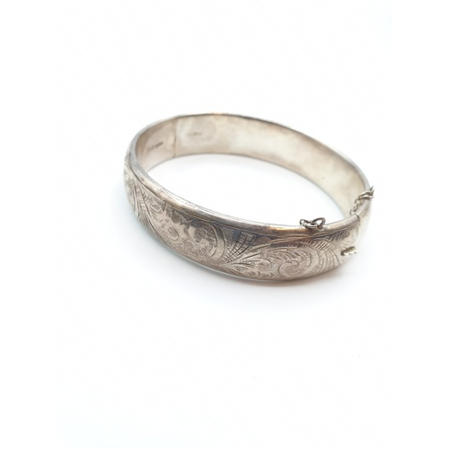 12 - Hallmarked silver bangle patterned on one side, approx 7cm diameter at widest point, weight 28.5g...