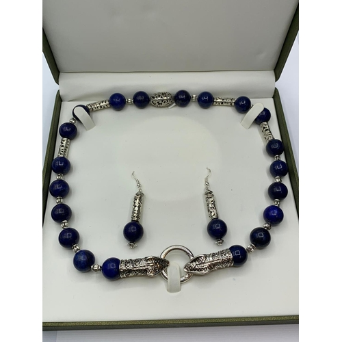 146 - A lapis lazuli and Tibetan Style silver necklace and earrings set in a    presentation box. Necklace...