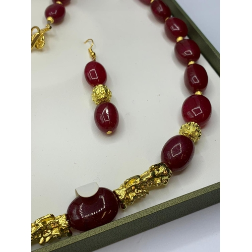 24 - An impressive, large beaded, ruby and gold filled necklace and earrings set in a presentation box. N...