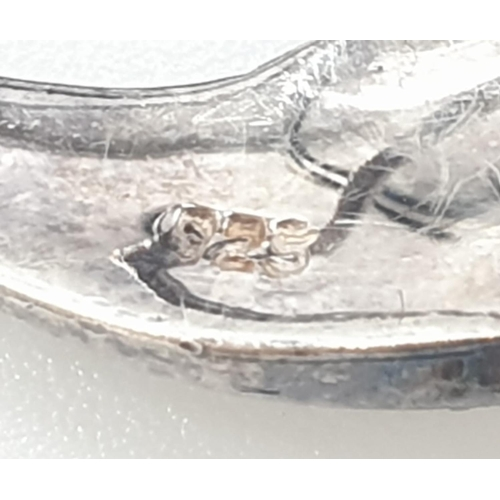 174 - Silver marcasite and mother of pearl dolphin brooch, having a garnet eye with mother of pearl tail a...