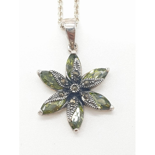 339 - Silver peridot and marcasite flower pendant on silver chain, pendant consisting 6 faceted peridot st...