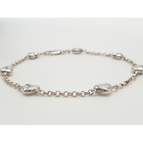 445 - Silver heart bracelet having seven hearts on a fine silver belcher chain, bracelet marked 925 silver...