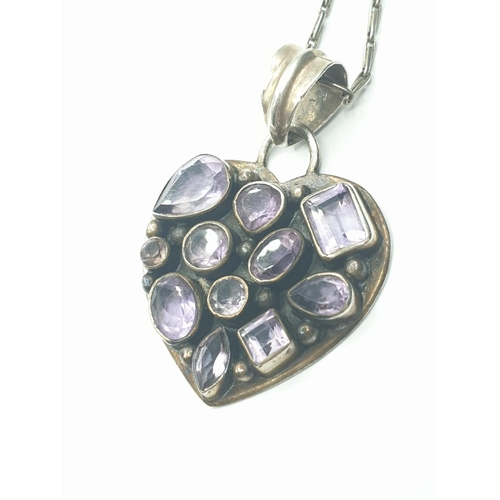 447 - Silver heart shaped pendant and silver chain, pendant encrusted with amethyst of various shapes, pen...