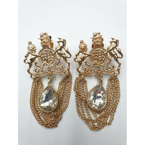 565 - A statement pair of earrings with the British Royal Coat of Arms and a trilogy of rings with clear s...