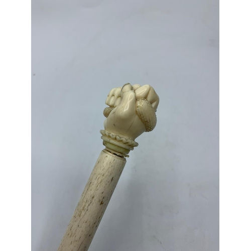 573 - 19th century whale bone walking stick with carved hand holding serpent, 83cm long approx
