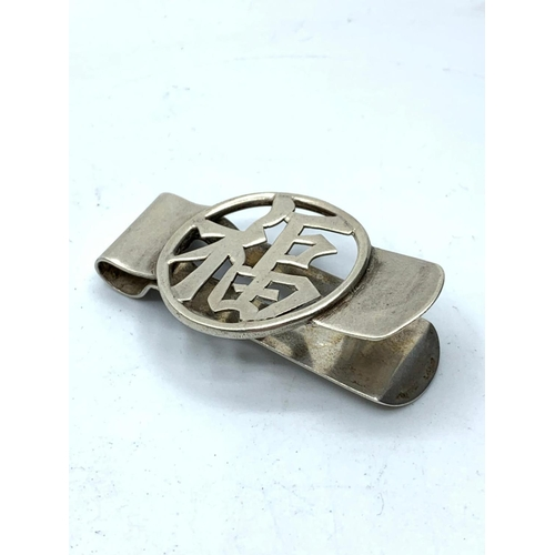 587 - Silver Chinese engraved money clip, 17.2g weight and 5.5cm long approx