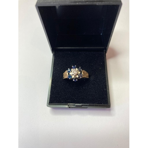 754 - 9ct Gold and Sapphire ring having six sapphires in a flower setting with illusion set diamond to cen...