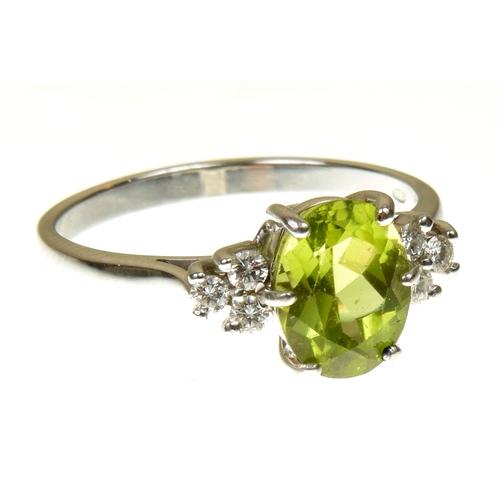 12 - An 18ct  gold peridot and diamond dress ring The oval shape peridot with brilliant cut diamond trefo...