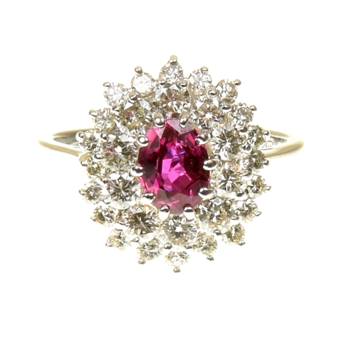 9 - A ruby and diamond cluster ring The oval shape ruby within a brilliant cut diamond tiered surround, ...