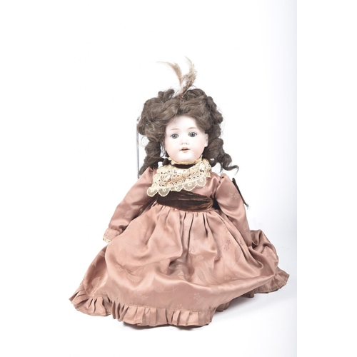 1 - A German bisque headed doll With dark brown curly wig, open/shut blue eyes, open mouth, impressed ma...