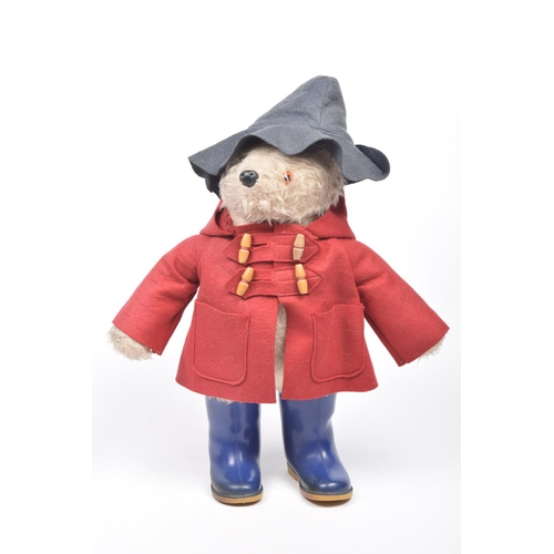 18 - A light brown plush Paddington Bear With glass button eyes, in dark grey hat, red dufflecoat and blu...