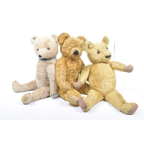 19 - Three plush teddy bears  Comprising a gold plush Merrythought bear with glass eyes and articulated l...
