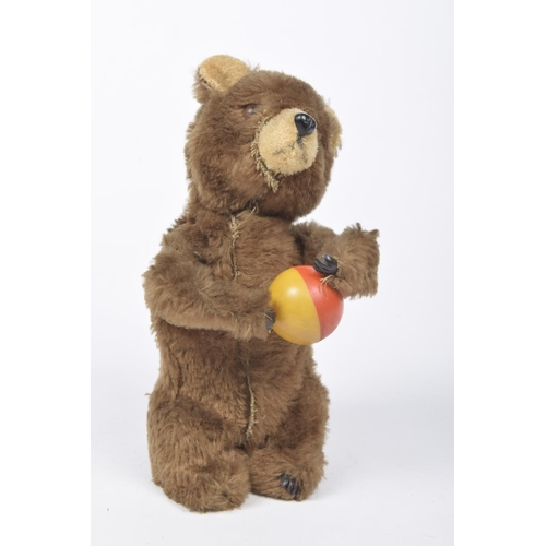 20 - A brown plush clockwork bear holding yellow and red ball Probably Schuco, height 19cm...
