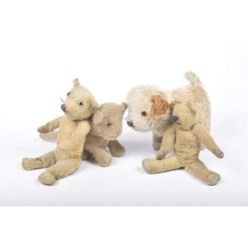21 - Four gold plush items  Comprising a plush lion cub with glass eyes - seated, height 15cm, a brown an...