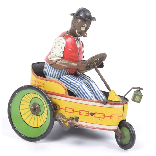 52a - A tinplate clockwork Lehmann tricycle In red and yellow, with green and yellow wheels, with a black ...