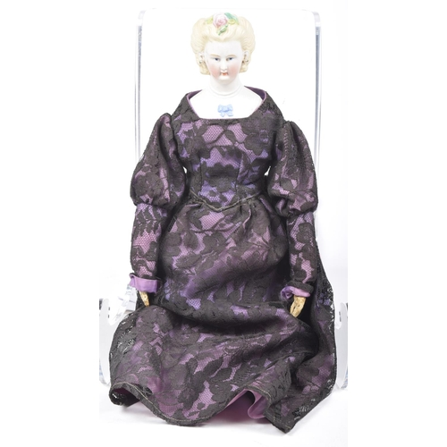 6 - A 19th Century bisque shoulder doll With moulded hair, blue painted eyes, moulded blouse with blue b...