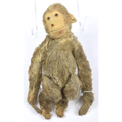 9 - A Steiff brown plush monkey With glass eyes, felt face, ears, hands and feet, with pin to left ear, ...