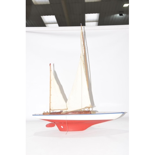 55a - A modern pond yacht  With red and white fiberglass hull and wooden deck with two masks and sails, le...