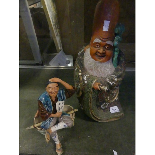 13 - A Japanese satsuma figure of a wise man together with a further ceramic figure of a man seated on bu...