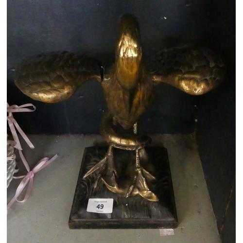 49 - A gilt metal model of a crane wrestling a snake, raised on a plinth base (af)...