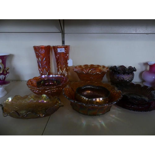 57 - A collection of orange and blackberry tinted Carnival glass, to include a pair of floral decorated v...