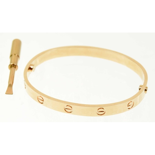 11 - A Cartier 'Love' bangle Designed as a series of screw head motifs with screw fitting, signed and num...