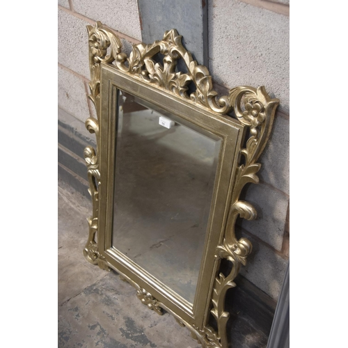 15 - An ornate carved giltwood beveled wall mirror....