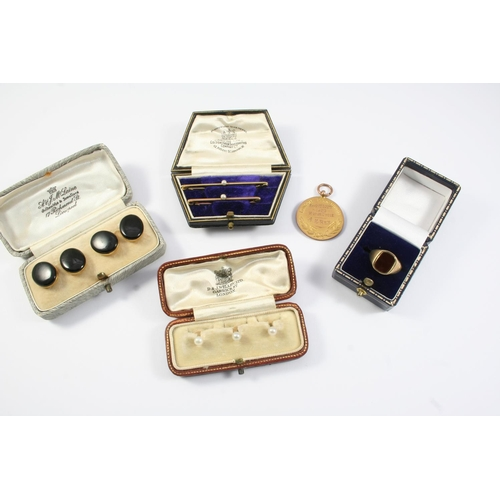 1656 - A PAIR OF BLACK ONYX AND GOLD CUFFLINKS each link formed with an oval section of black onyx backed i...