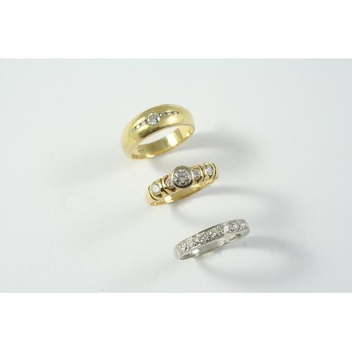 1699 - A DIAMOND SOLITAIRE RING the circular-cut diamond is collet set, with two circular-cut diamonds to e...