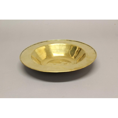 2214 - A LATE 17th/18th CENTURY BRASS DISH. A Brass dish of circular form with deep central well and broad ...
