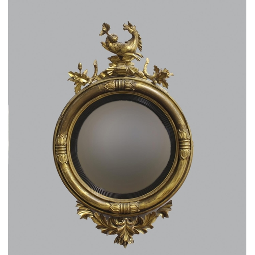 2250 - A REGENCY GILT WOOD CONVEX MIRROR, the circular convex mirror plate within an ebonised moulded fille...