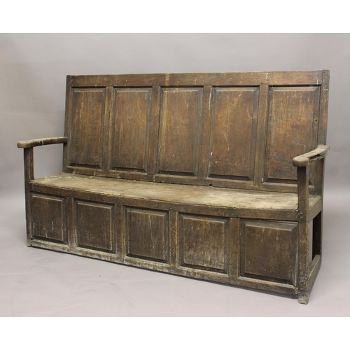 2281 - AN 18TH CENTURY OAK SETTLE, with panelled back and slightly scrolling arms on a box base, height 102...