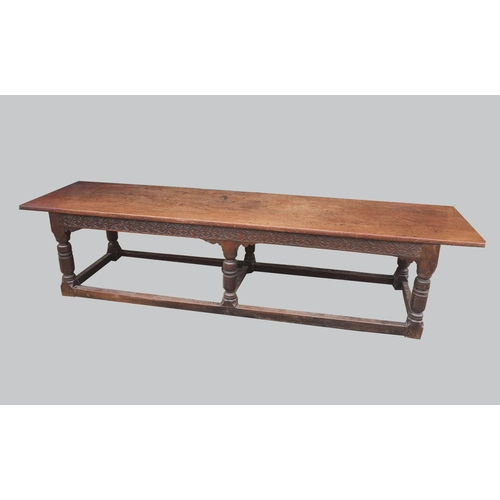 2284 - AN OAK AND WALNUT REFECTORY TYPE DINING TABLE. With a broad rectangular top on a moulded frieze rail...