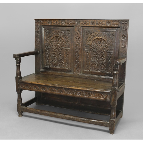 2291 - AN OAK SETTLE, late 17th century, the two-panelled back carved with leaves and flowers under archway...