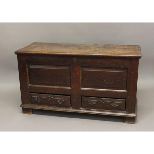 2292 - A GEORGE II OAK MULE CHEST. With a hinged rectangular lid with moulded border above a two panel fron...