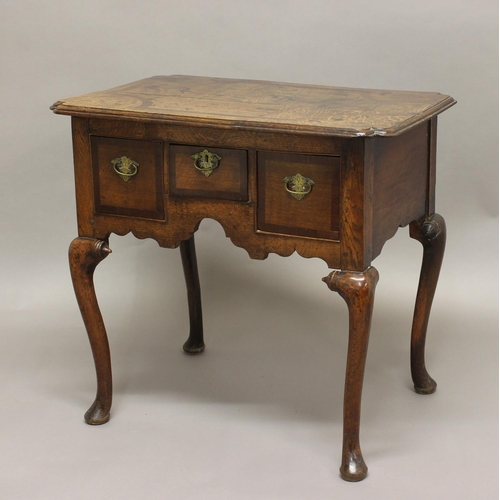 2310 - AN 18TH CENTURY OAK LOWBOY, the inlaid shaped rectangular top above three drawers on a carved frieze...