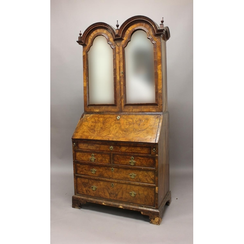 2343 - A GEORGE I WALNUT DOUBLE DOME TOPPED BUREAU BOOKCASE. The double domed top with deep moulding and tu...