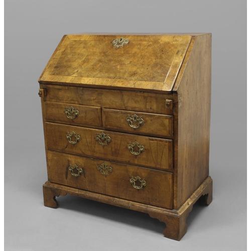 2393 - A GEORGE I WALNUT VENEERED BUREAU. An early 18th century walnut veneered bureau with a sloping fall ...
