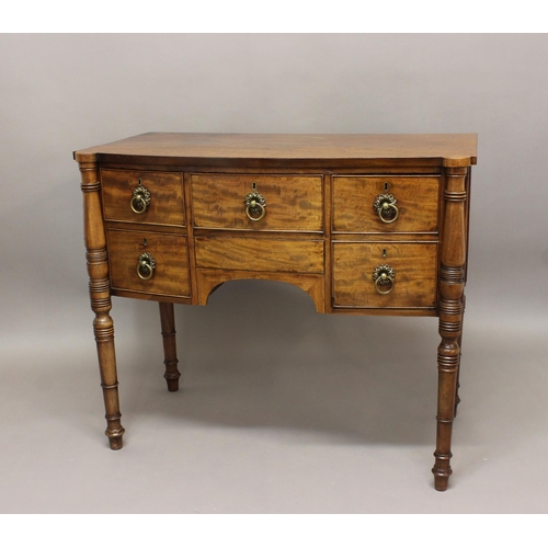 2401 - A LATE GEORGE III MAHOGANY SIDEBOARD. A bow fronted mahogany sideboard with a shaped top on pillar f...