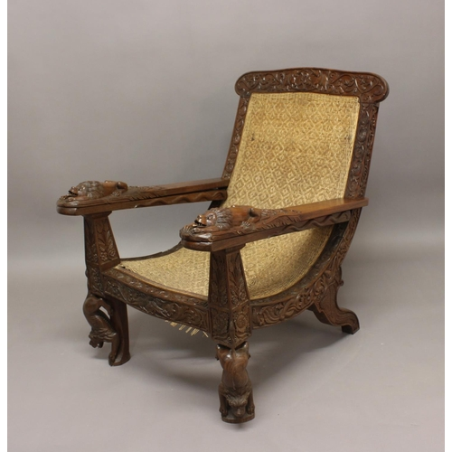 2408 - A LATE 19TH/EARLY 20TH CENTURY TEAK PLANTERS CHAIR. A teak planters chair with elaborately carved fr...