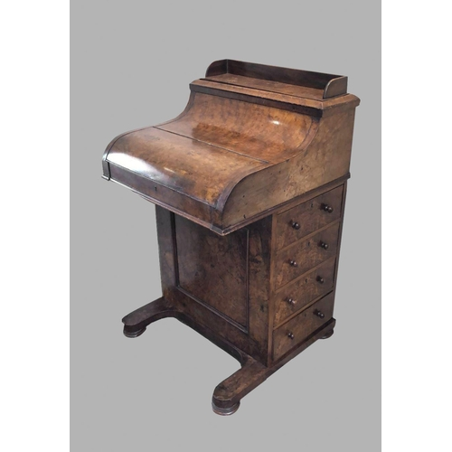 2414 - A VICTORIAN BURR WALNUT PIANO FRONTED DAVENPORT. The sliding writing surface releasing a pop-up stat...