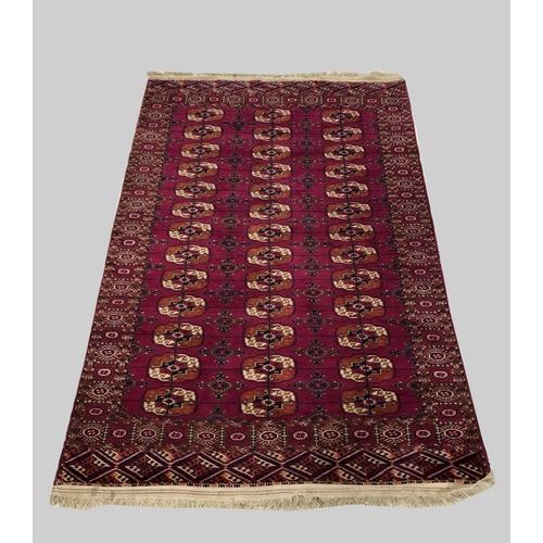 2443 - A TEKKE RUG, Emirate of Bukhara, c.1910, the raspberry field with three columns of quartered guls en...