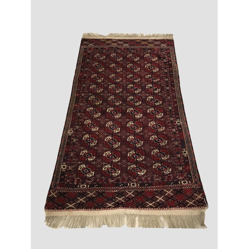 2476 - A TEKKE TURKMEN RUG, c.1900, Emirate of Bukhara, the maroon field with four columns of quartered gul...
