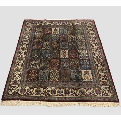 2477 - AN INDIAN CARPET, the compartmentalised field of polychrome flowering plants enclosed by ivory borde...