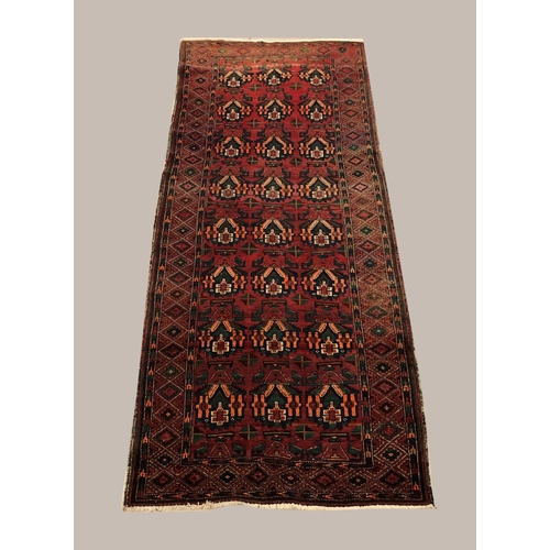 2480 - BALOUCH LONG RUG the abrashed raspberry field of stylised plants enclosed by borders of stepped meda...