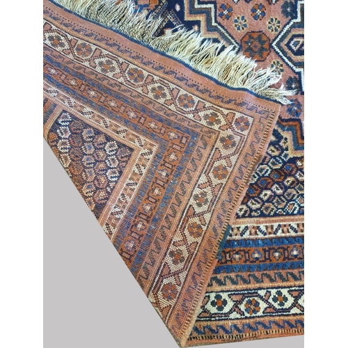 2458 - AN AFSHAR RUG, c.1910, South East Iran, the pale brick red field with three stepped indigo medallion...