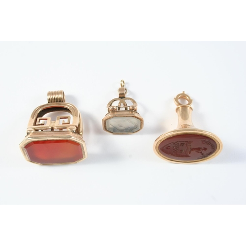 1155 - THREE ASSORTED GOLD SEALS one with carnelian matrix engraved with a coat of arms, 3.7cm high, one wi...