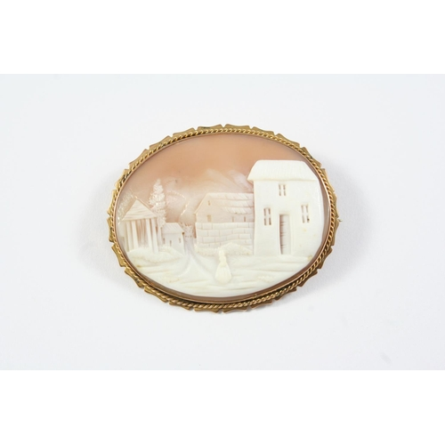1215 - A CARVED SHELL CAMEO OVAL SHAPED BROOCH depicting a rural mountainous scene, in a gold mount, 4.8cm ...