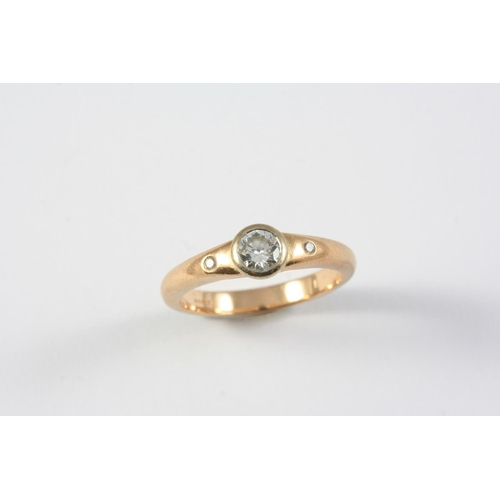 1332 - A DIAMOND SOLITAIRE RING the collet set circular-cut diamond is mounted with two small diamonds on a...